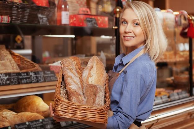 Mulher jovem e atraente sorrindo, gostando de trabalhar em sua padaria, vendendo pães deliciosos