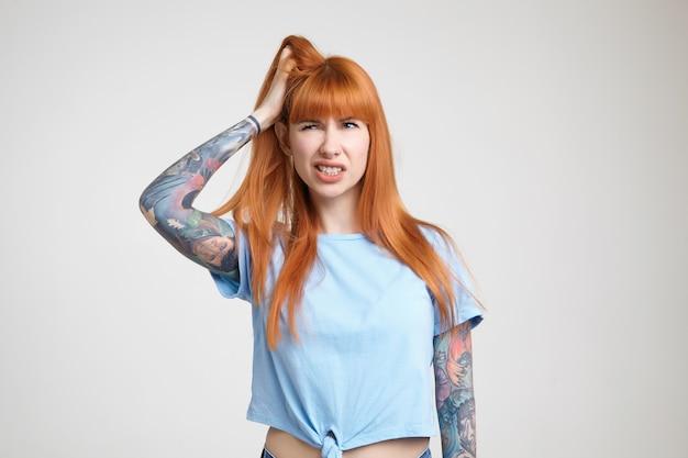 Mulher jovem e atraente tatuada descontente, segurando a cabeça com a mão levantada e rosto carrancudo enquanto olha para o lado, isolado sobre fundo branco