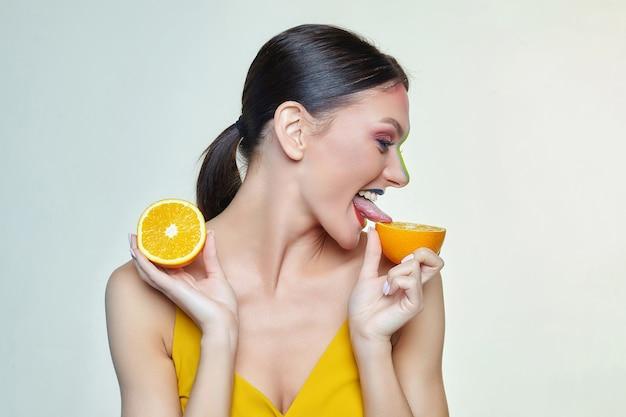 Mulher jovem e atraente tocando com a língua uma fatia de laranja