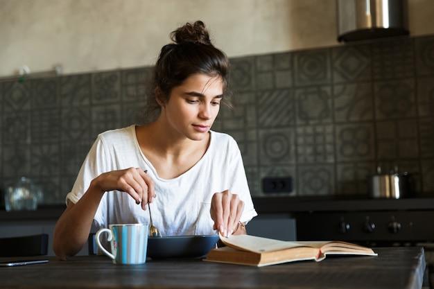 Mulher jovem e atraente tomando café da manhã saudável na cozinha de casa, lendo um livro