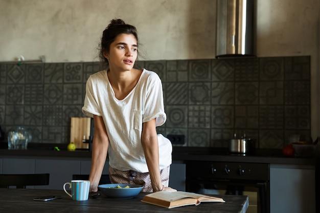 Mulher jovem e atraente tomando café da manhã saudável na cozinha de casa