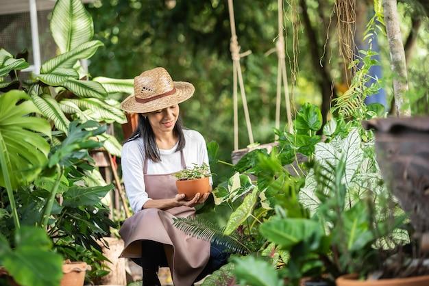 Mulher jovem e atraente trabalhando com plantas decorativas no centro de jardim. supervisor feminino examinando plantas em jardinagem fora na natureza de verão. lindo jardineiro sorrindo. cuidados com as plantas.