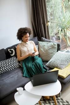 Mulher jovem e atraente trabalhando no laptop e usando o celular em casa