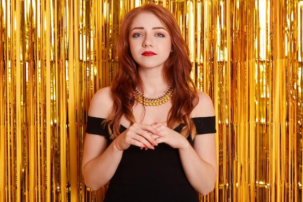 Mulher jovem e atraente, triste, em um vestido preto, sentindo-se insatisfeita, isolada, decorada com uma parede de ouropel dourado, olhando para a câmera com olhar triste