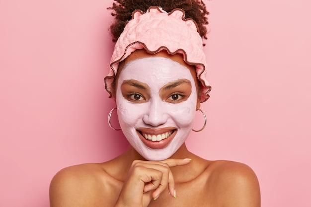 Mulher jovem e atraente usa bandana de banho, olha positivamente para a câmera, sorri suavemente, fica nua e posa sobre a parede rosa