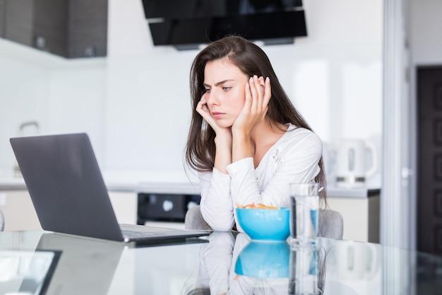 Mulher jovem e atraente usando laptop no café da manhã e sentado na cozinha.