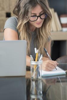 Mulher jovem e atraente usando óculos e tomando notas enquanto está sentado em frente ao laptop na mesa em casa, linda mulher escrevendo no caderno. mulher fazendo anotações enquanto usa um laptop e trabalha online