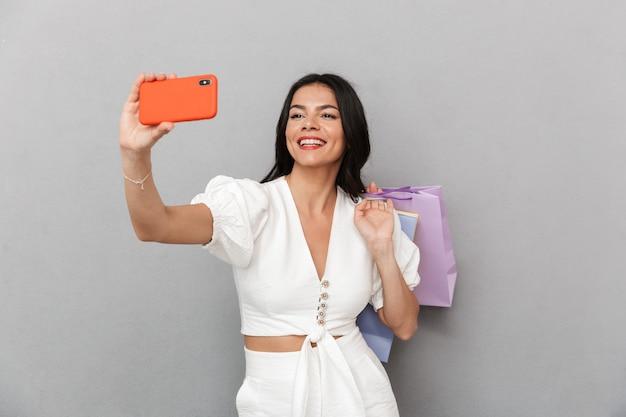 Mulher jovem e atraente usando roupa de verão em pé, isolada na parede cinza, tirando uma selfie e carregando sacolas de compras