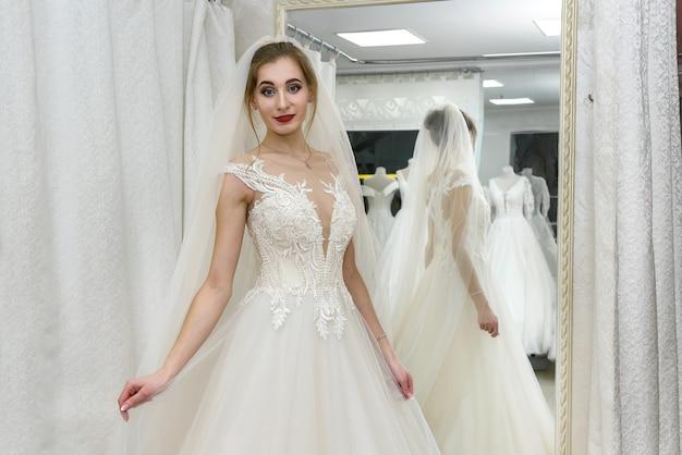 Mulher jovem e atraente usando vestido de noiva em loja de noivas