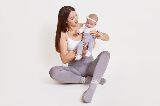 Mulher jovem e atraente vestindo leggins cinza e camiseta sem mangas, sentado no chão com o filho recém-nascido, mulher de cabelos escuros carrega sua filha, criança com hairband, isolado na parede branca.