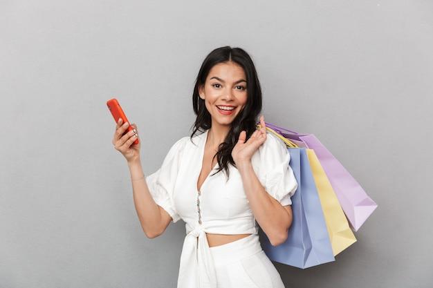 Mulher jovem e atraente vestindo roupa de verão em pé, isolada na parede cinza, carregando sacolas de compras e segurando um telefone celular