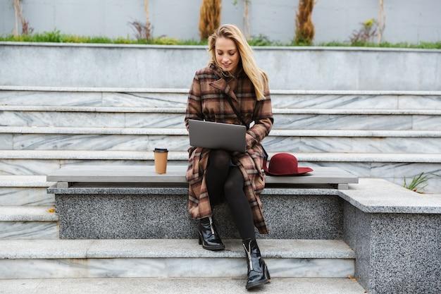 Mulher jovem e atraente vestindo um casaco sentada ao ar livre, usando um laptop