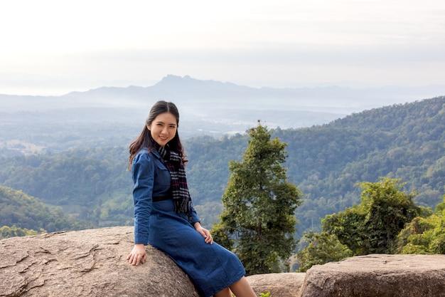 Mulher jovem e atraente viajante asiática em pé olhando para a paisagem do vale da montanha, paisagem de verão, sentindo paz, alegria, sucesso feliz