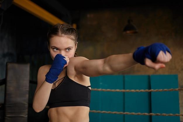 Mulher jovem e autodeterminada boxeadora profissional com braços musculosos e abdominais fortes, vestindo blusa esportiva preta e bandagens de boxe azuis, dominando a técnica de punção