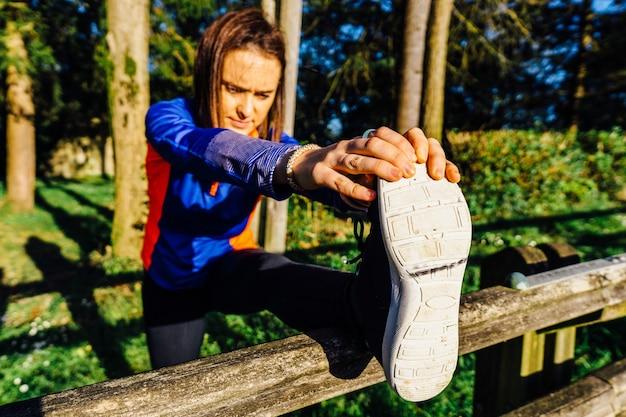 Mulher jovem e bela adulta esticando os tendões dos pés e tocando os dedos dos pés em um parque arborizado no ponto do pôr do sol conceito esporte fim de semana afterwork