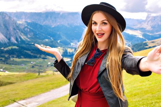Mulher jovem e bem alegre, turista, vestindo uma jaqueta de couro elegante e um chapéu da moda, mostrando uma vista incrível das montanhas dos alpes austríacos