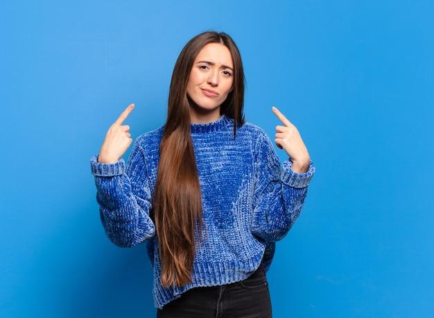 Mulher jovem e bem casual com uma atitude ruim, parecendo orgulhosa e agressiva, apontando para cima ou fazendo um sinal divertido com as mãos
