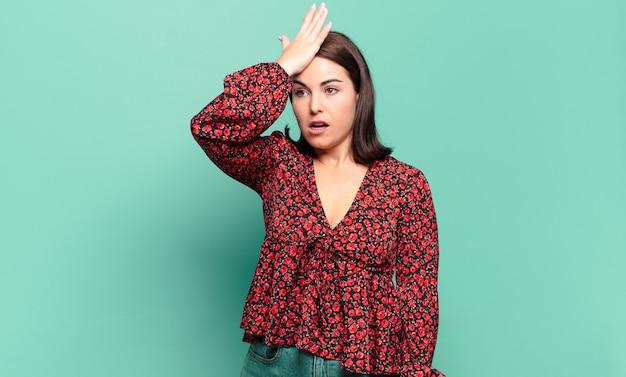 Mulher jovem e bem casual levantando a palma da mão na testa pensando, opa, depois de cometer um erro estúpido ou se lembrar, sentindo-se idiota