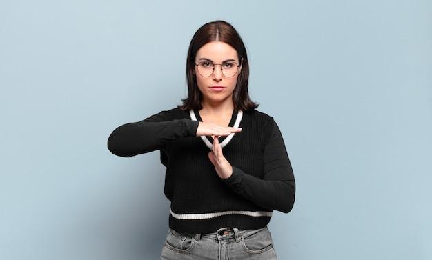 Mulher jovem e bem casual, parecendo séria, severa, irritada e descontente, fazendo sinal de castigo