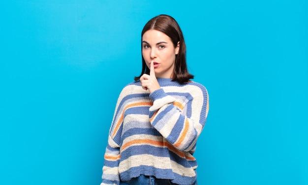 Mulher jovem e bem casual pedindo silêncio e silêncio, gesticulando com o dedo na frente da boca, dizendo shh ou guardando um segredo