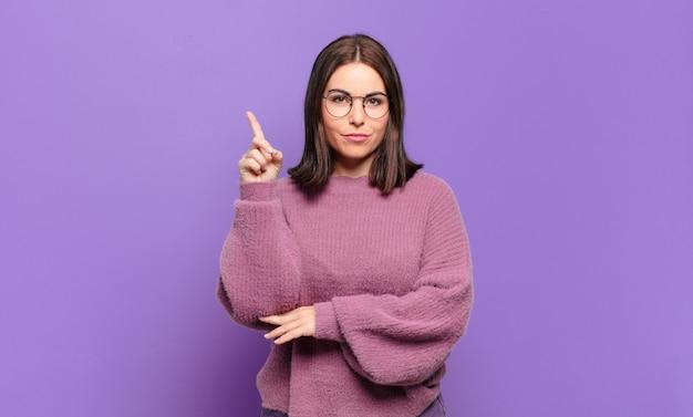 Mulher jovem e bem casual se sentindo como um gênio, segurando o dedo com orgulho no ar depois de realizar uma grande ideia, dizendo eureka