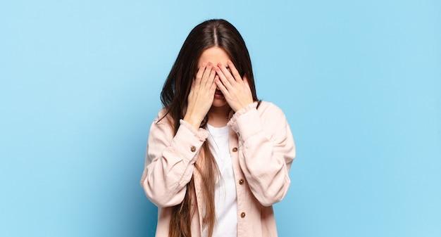 Mulher jovem e bem casual sentindo-se triste, frustrada, nervosa e deprimida, cobrindo o rosto com as duas mãos, chorando