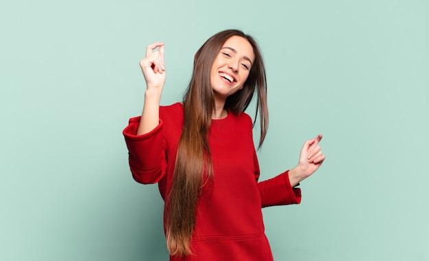 Mulher jovem e bem casual sorrindo, sentindo-se despreocupada, relaxada e feliz, dançando e ouvindo música, se divertindo em uma festa