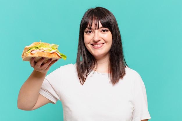 Mulher jovem e bem curvilínea com expressão feliz e segurando um sanduíche