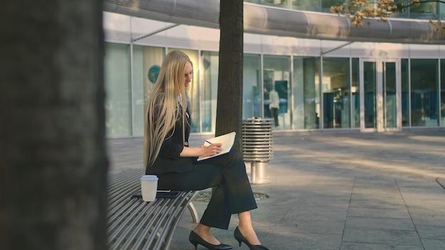 Mulher jovem e bem sucedida a tomar notas ao ar livre.