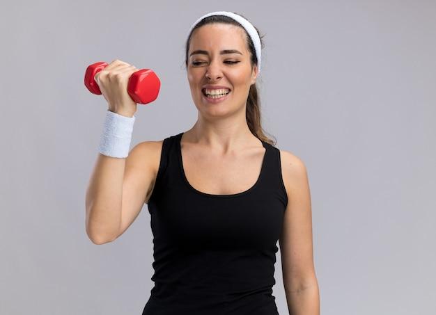 Mulher jovem e bem tensa e esportiva usando bandana e pulseiras levantando halteres olhando para ela