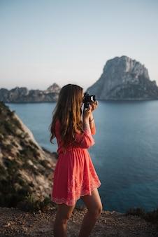 Mulher jovem e bonita à beira-mar tirando uma foto com uma câmera