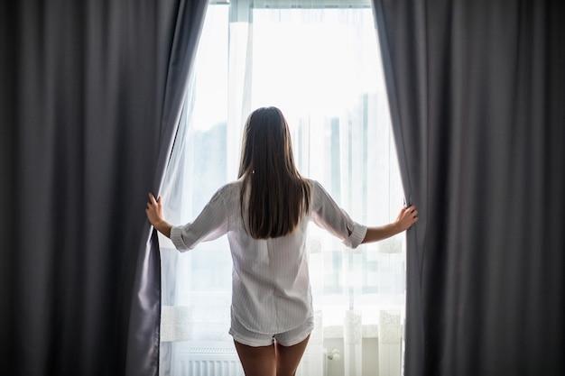 Mulher jovem e bonita abrindo as cortinas e olhando pela janela