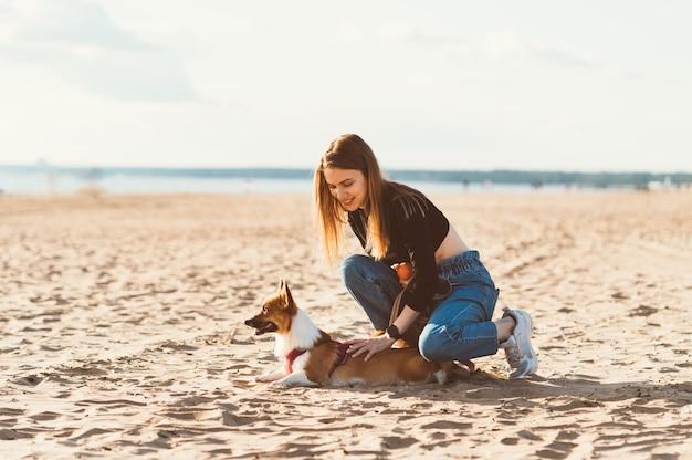 Mulher jovem e bonita acariciando o cachorrinho corgi, descansando na praia. mulher andando com cachorro