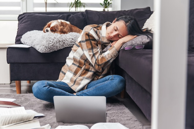 Mulher jovem e bonita adormeceu em casa enquanto trabalhava no laptop. menina e cachorro dormindo em casa