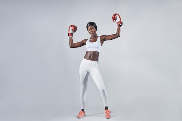Mulher jovem e bonita africana usando luvas de boxe, mantendo os braços levantados