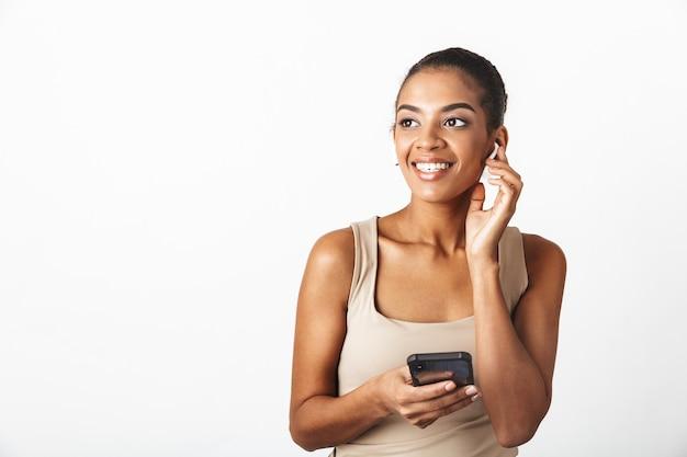 Mulher jovem e bonita africana vestida casualmente em pé, isolada no branco, usando fones de ouvido sem fio, usando telefone celular