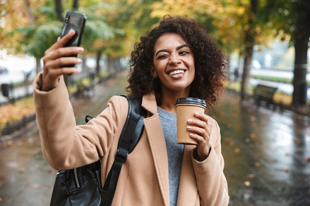 Mulher jovem e bonita africana vestindo um casaco, caminhando ao ar livre no parque, carregando uma mochila, tirando uma selfie