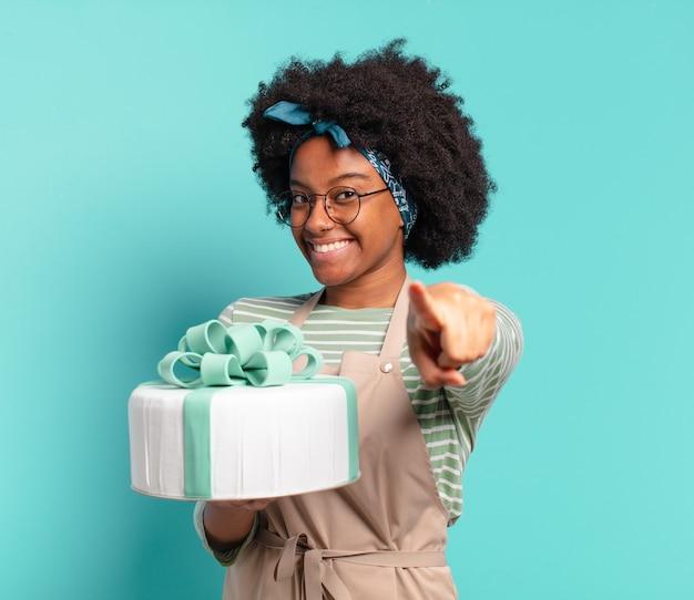 Mulher jovem e bonita afro padeiro com um bolo de aniversário