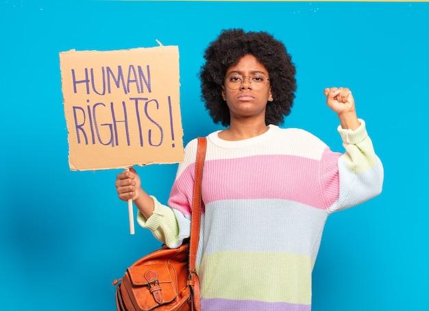 Mulher jovem e bonita afro protestando com faixa dos direitos humanos