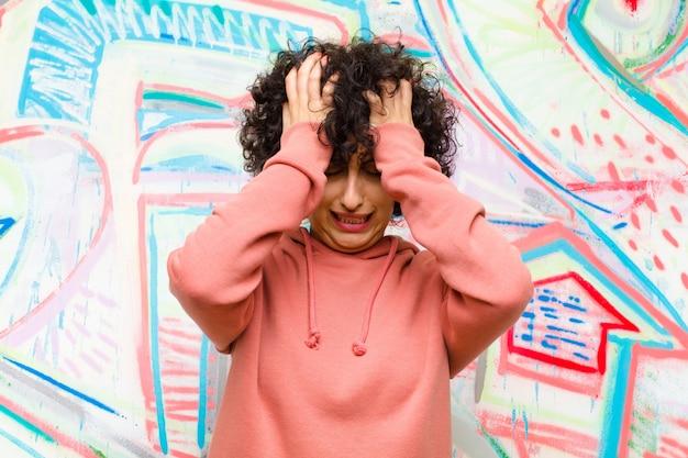 Mulher jovem e bonita afro se sentindo estressada e ansiosa, deprimida e frustrada com dor de cabeça, levantando as duas mãos contra a parede do graffiti