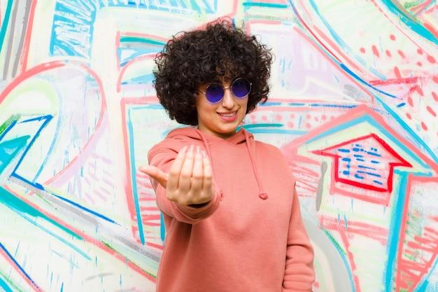 Mulher jovem e bonita afro se sentindo feliz, bem-sucedida e confiante, enfrentando um desafio e dizendo: traga-o! ou recebê-lo contra a parede de graffiti