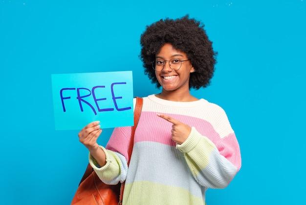 Mulher jovem e bonita afro segurando um banner de conceito grátis