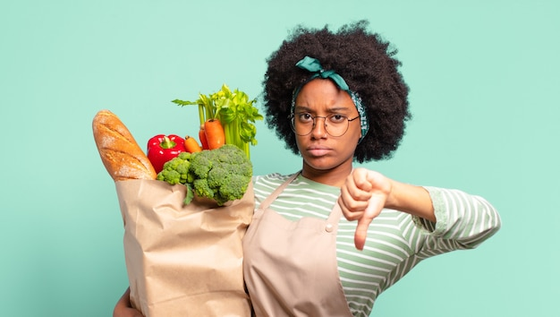 Mulher jovem e bonita afro sorrindo e parecendo feliz, despreocupada e positiva, gesticulando vitória ou paz com uma das mãos e segurando uma sacola de legumes