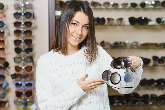 Mulher jovem e bonita ajustando seus novos óculos de sol na loja de ótica