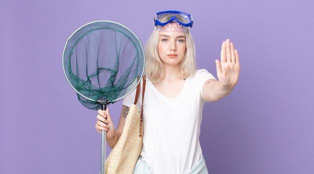 Mulher jovem e bonita albina com cara de sério, mostrando a palma da mão aberta, fazendo gesto de pare com óculos de proteção e uma rede de pesca