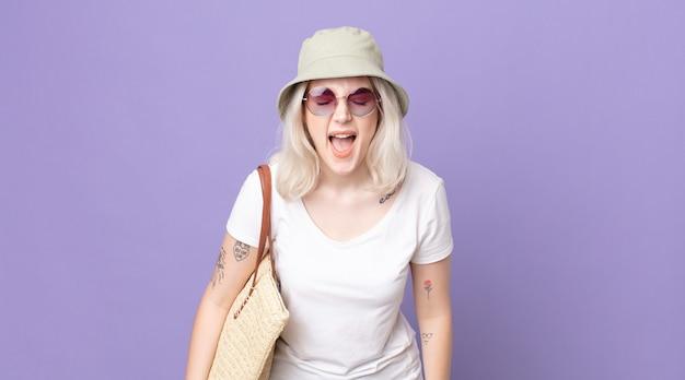 Mulher jovem e bonita albina gritando agressivamente, parecendo muito zangada. conceito de verão