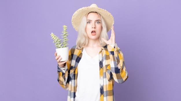 Mulher jovem e bonita albina gritando com as mãos para o alto e segurando um cacto de planta de casa