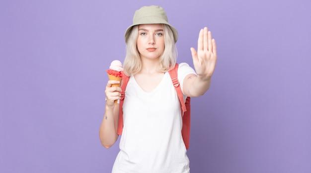 Mulher jovem e bonita albina olhando séria, mostrando a palma da mão aberta, fazendo gesto de parada.
