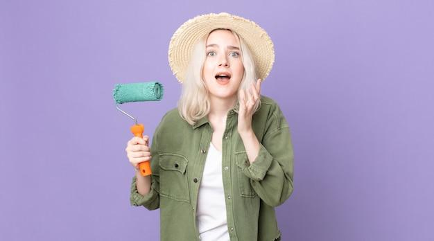 Mulher jovem e bonita albina parecendo desesperada, frustrada e estressada segurando um rolo de tinta