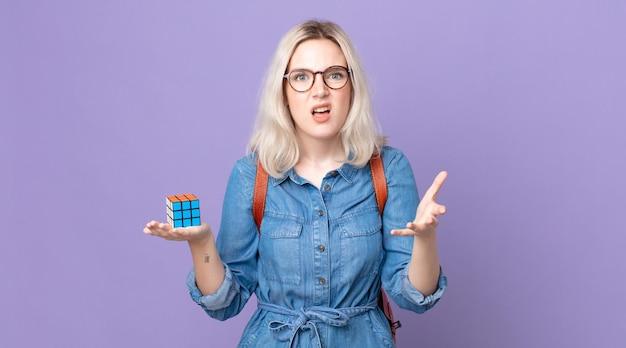 Mulher jovem e bonita albina parecendo zangada, irritada e frustrada, resolvendo um jogo de inteligência